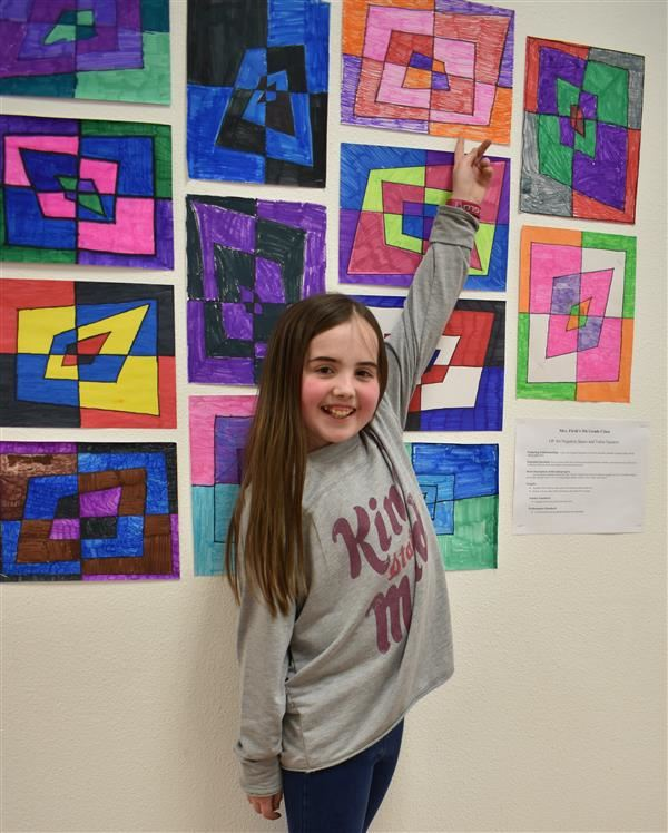 girl student pointing to artwork